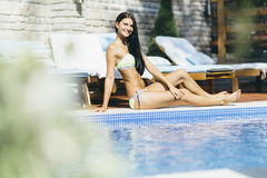 Beautiful young woman sunbathing at the poolside Royalty Free Stock Image