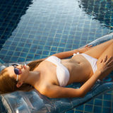Beautiful woman sunbathing in swimming pool Royalty Free Stock Image