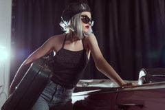Beautiful young woman in sunglasses and beret holding vintage suitcase and looking away while leaning at classic. Car royalty free stock image