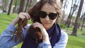 Beautiful young woman in sunglasses braids plait in summer park stock footage