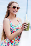 Beautiful young woman with sunglasses drinking green vegetable smoothie. stock images
