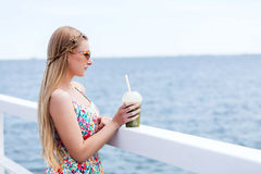 Beautiful young woman with sunglasses drinking green vegetable smoothie. Royalty Free Stock Images
