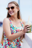 Beautiful young woman with sunglasses drinking green vegetable smoothie. Stock Photos