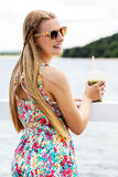 Beautiful young woman with sunglasses drinking green vegetable smoothie. Royalty Free Stock Photo