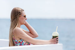 Beautiful young woman with sunglasses drinking green vegetable smoothie. stock photography