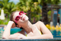 Beautiful young woman in sunglasses with exotic cocktail in luxury pool Royalty Free Stock Photography