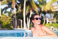 Beautiful young woman in sunglasses in luxury spa pool. Remote tropical beaches and countries. travel concept Royalty Free Stock Image