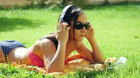 Beautiful young woman in sunglasses lying on the grass, listening to music uses mobile phone and singing song. 3840x2160 stock video footage