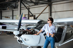 Beautiful young woman in sunglasses posing near plane in angar Royalty Free Stock Photography