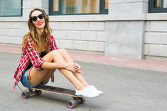 Beautiful young woman in sunglasses seat on skate, street fashion lifestyle. Royalty Free Stock Photos