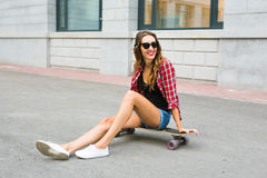 Beautiful young woman in sunglasses seat on skate, street fashion lifestyle. Stock Photos