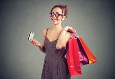 Beautiful young woman in sunglasses with shoppping bags and credit card. Smiling Stock Image