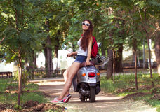 A beautiful young woman with sunglasses sitting on a scooter Royalty Free Stock Image
