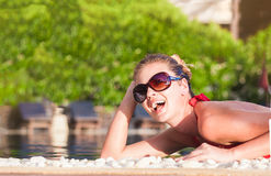 Beautiful young woman in sunglasses smiling in luxury pool Stock Images
