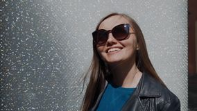 Beautiful young woman in sunglasses stands near the wall with crystals. Brilliant faceted stones, rhinestones shimmer. Amazingly in the sun. Fashion background stock video footage
