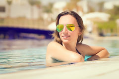 Beautiful young woman in sunglasses at the swimming pool Stock Images