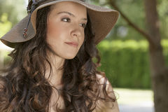 Beautiful young woman in sunhat looking away in park Royalty Free Stock Photos