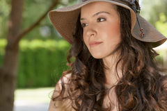 Beautiful young woman in sunhat looking away in park Stock Image