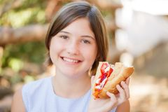 Pretty girl with tasty fast food outdoors. Picnic on the nature. Stock Images