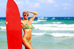 Beautiful young woman surfer girl in bikini with red surfboard a Royalty Free Stock Photography