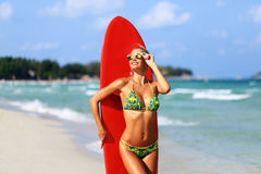 Beautiful young woman surfer girl in bikini with red surfboard a Royalty Free Stock Image