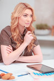 Beautiful young woman surfing in net. Deep in thoughts. Young attractive woman looking away while working with digital tablet at her work place at home Stock Image