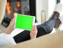 Young woman using tablet computer in front of fireplace Stock Photo