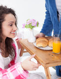 Beautiful young woman surprised by partner bringing breakfast in Royalty Free Stock Photography