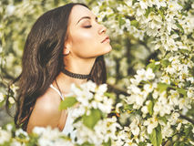 Beautiful young woman surrounded by flowers of apple-tree Royalty Free Stock Photography