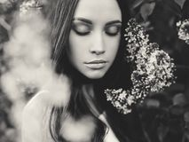 Beautiful young woman surrounded by flowers of lilac. Black and white outdoor fashion photo of beautiful young woman surrounded by flowers of lilac. Spring Stock Image