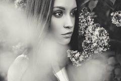 Beautiful young woman surrounded by flowers of lilac. Black and white outdoor fashion photo of beautiful young woman surrounded by flowers of lilac. Spring Stock Images
