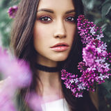 Beautiful young woman surrounded by flowers of lilac Stock Photography