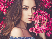 Beautiful young woman surrounded by flowers Royalty Free Stock Photos