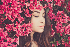 Beautiful young woman surrounded by flowers Stock Image