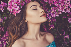Beautiful young woman surrounded by flowers Royalty Free Stock Images