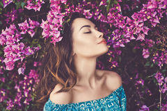 Beautiful young woman surrounded by flowers Stock Photos