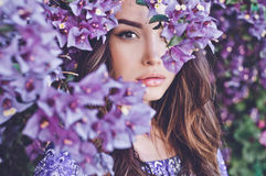 Beautiful young woman surrounded by flowers Stock Photo