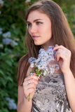 Beautiful young woman suspicious & flowers Royalty Free Stock Photography