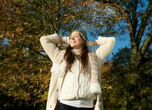 Beautiful young woman in sweater and hat relaxing outdoors Stock Photography