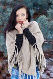 Beautiful young woman in sweater and jeans freezing forest in winter near trees Royalty Free Stock Photos