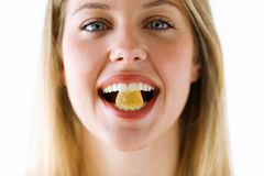 Beautiful young woman with a sweet candy in mouth looking at camera over white background. royalty free stock image