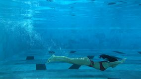 Beautiful young woman swimming under water in pool. Shot in 4k, suitable for commercial use stock video footage