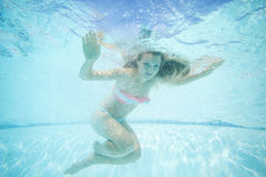 Beautiful young woman swimming underwater in pool. Royalty Free Stock Photos