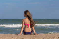 Beautiful young woman in a swimsuit with long hair sits on the beach near the sea Royalty Free Stock Photos