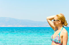 Beautiful young woman in swimsuit, relaxing on a tropical sunny beach Royalty Free Stock Photo