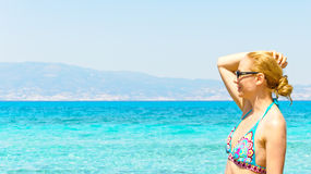 Beautiful young woman in swimsuit, relaxing on a tropical sunny beach Royalty Free Stock Image