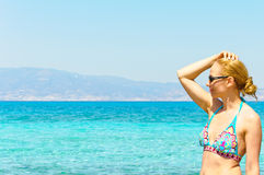 Beautiful young woman in swimsuit, relaxing on a tropical sunny beach Stock Photos