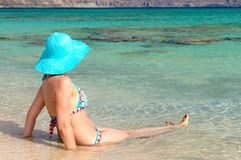 Beautiful young woman in swimsuit with sunhat, relaxing on the sunny beach Royalty Free Stock Images