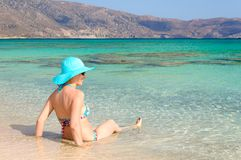 Beautiful young woman in swimsuit with sunhat, relaxing on the sunny beach Stock Images
