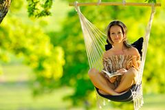 Beautiful young woman swinging outdoor Royalty Free Stock Photos